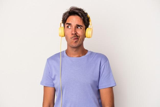 Jeune homme métis écoutant de la musique isolée sur fond bleu confus, se sent dubitatif et incertain.