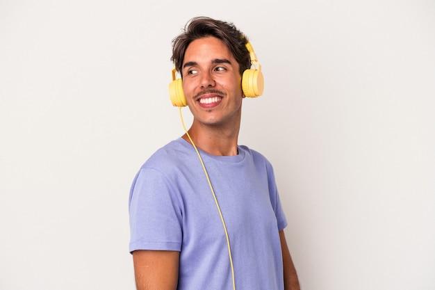 Jeune homme métis écoutant de la musique isolée sur fond bleu regarde de côté souriant, joyeux et agréable.