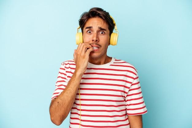 Jeune homme métis écoutant de la musique isolée sur fond bleu se rongeant les ongles, nerveux et très anxieux.