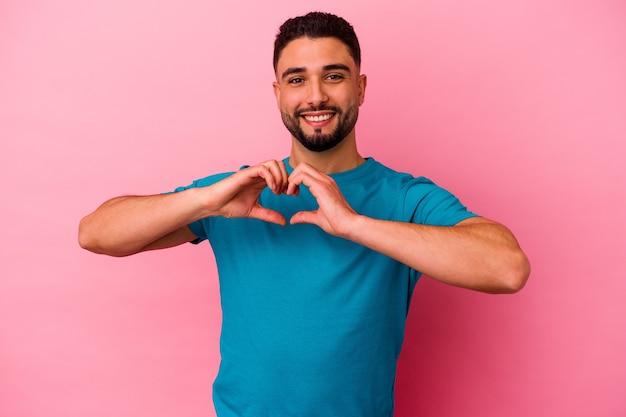Jeune homme métis isolé sur mur rose souriant et montrant une forme de coeur avec les mains.