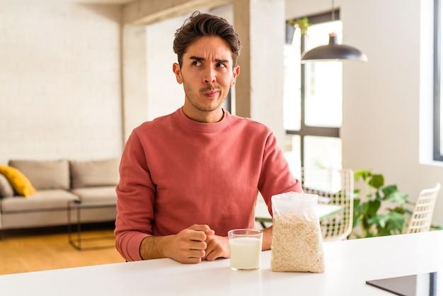 Jeune homme métis mangeant de la farine d'avoine et du lait pour le petit déjeuner dans sa cuisine confus, se sent dubitatif et incertain.