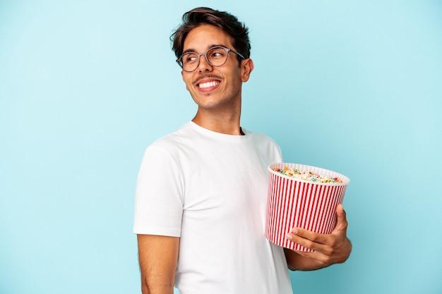 Jeune homme métis mangeant des pop-corns isolés sur fond bleu regarde de côté souriant, joyeux et agréable.
