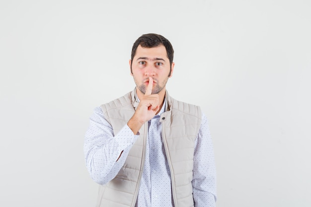 Jeune homme mettant l'index sur la bouche et montrant le geste de silence en veste beige et à la recherche de sérieux. vue de face.
