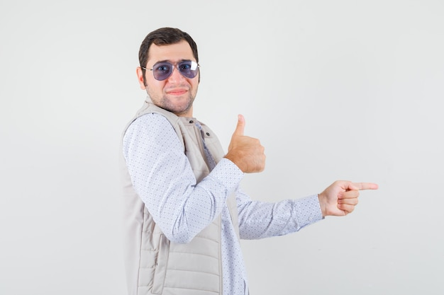 Jeune homme mettant des lunettes tout en pointant vers la droite avec l'index et montrant le pouce vers le haut en veste beige et casquette et à l'optimiste. vue de face.