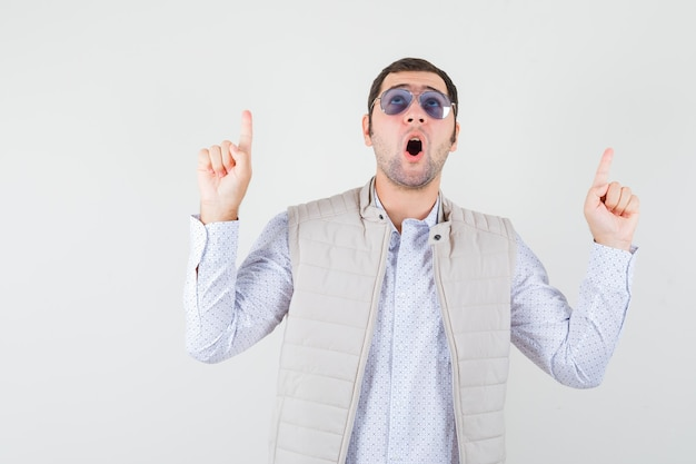 Jeune homme mettant des lunettes tout en pointant vers le haut avec l'index en veste beige et casquette et à la surprise, vue de face.
