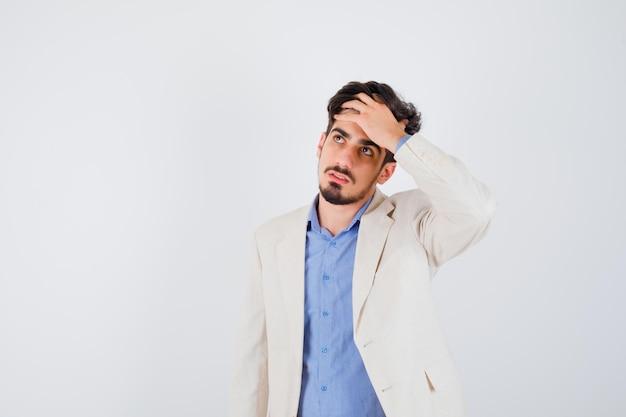 Jeune homme mettant la main sur le front, regardant loin en t-shirt bleu et veste de costume blanc et à l'air pensif
