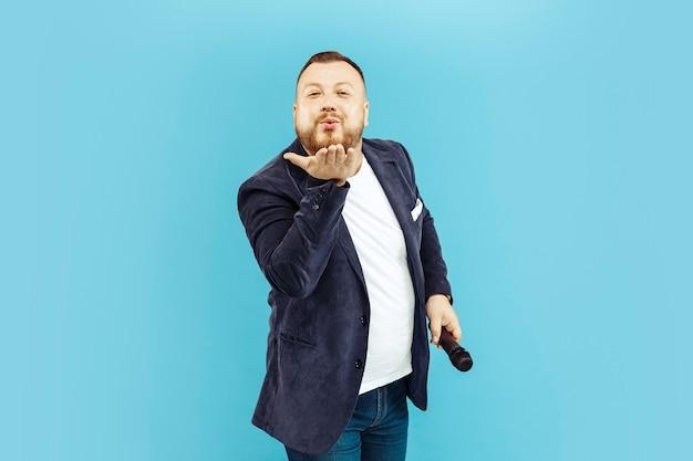 Jeune homme avec microphone sur bleu, concept de premier plan