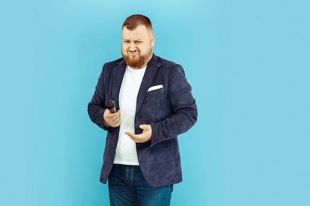 Jeune homme avec microphone sur l'espace bleu, concept principal