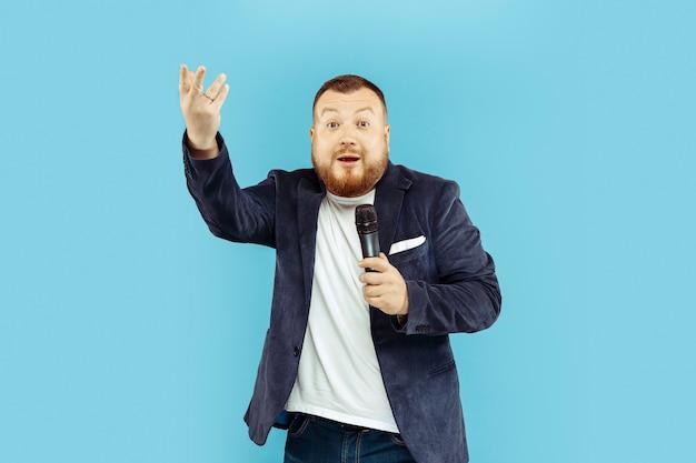 Jeune homme avec microphone sur studio bleu, concept de premier plan