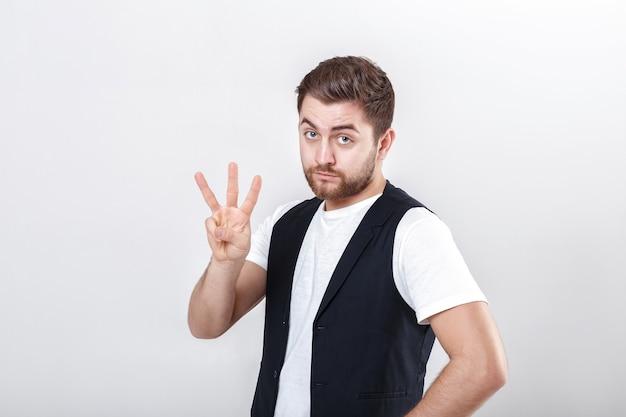 Jeune homme mignon avec une barbe dans une chemise blanche et un gilet noir montrant le geste numéro trois