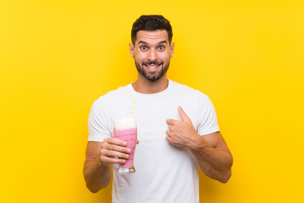 Jeune homme avec un milkshake à la fraise sur un mur jaune isolé avec une expression faciale surprise