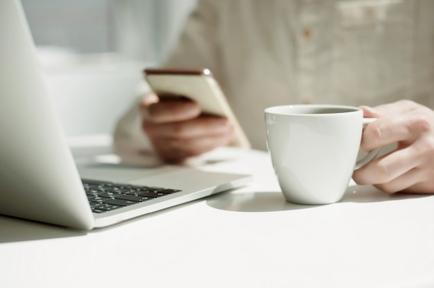 Un jeune homme millénaire travaille à distance sur un ordinateur portable.