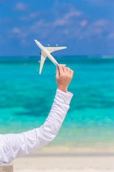 Jeune homme avec miniature d'un avion sur une plage tropicale