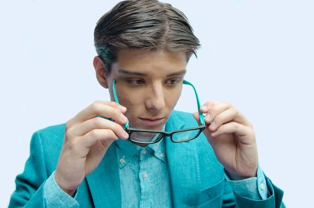 Jeune homme a mis des lunettes sur le visage. guy en costume bleu se préparer à lire.