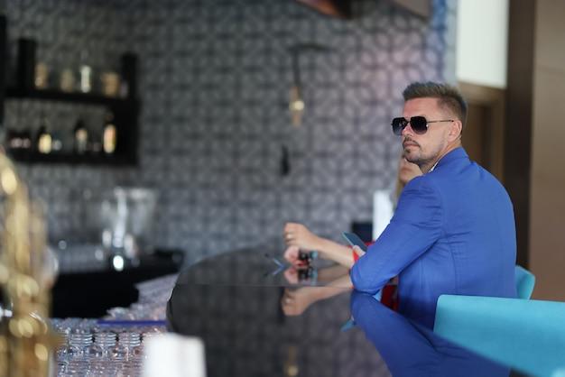 Jeune homme à la mode en attente de commande le bar de l'hôtel