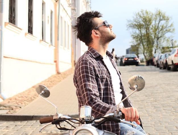 Jeune homme à la mode chevauchant un scooter vintage dans la rue