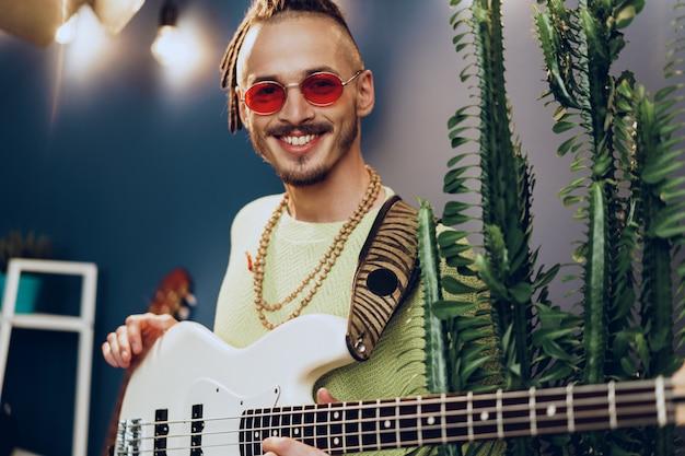Jeune homme à la mode en lunettes de soleil roses jouant de la guitare avec joie
