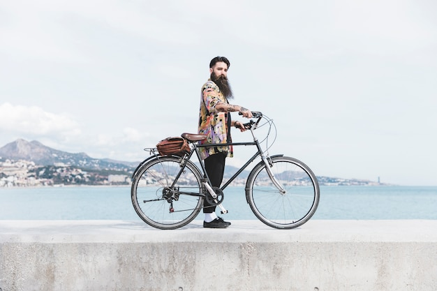 Jeune homme à la mode avec son vélo debout sur le brise-lames près de la côte