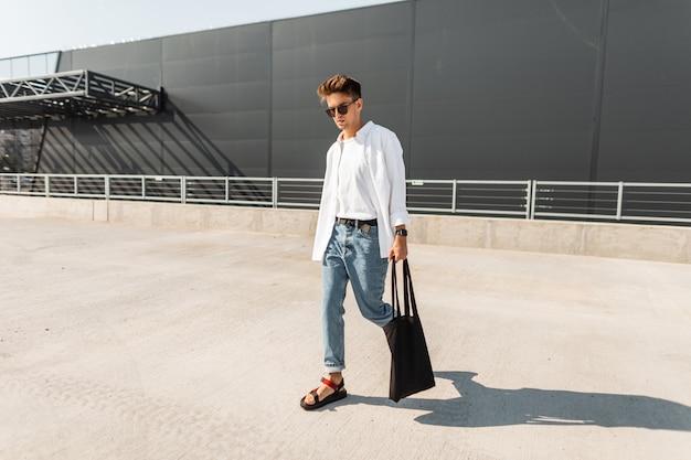 Jeune homme moderne en vêtements blancs et denim à la mode dans des lunettes de soleil en sandales rouges avec un sac vintage se promène dans la rue par une journée ensoleillée.