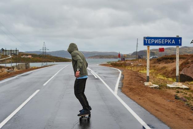 Jeune homme monté sur un longboard sur une route de montagne sinueuse vide en été, vue arrière.