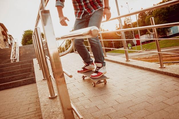 Jeune homme monté sur une planche à roulettes.