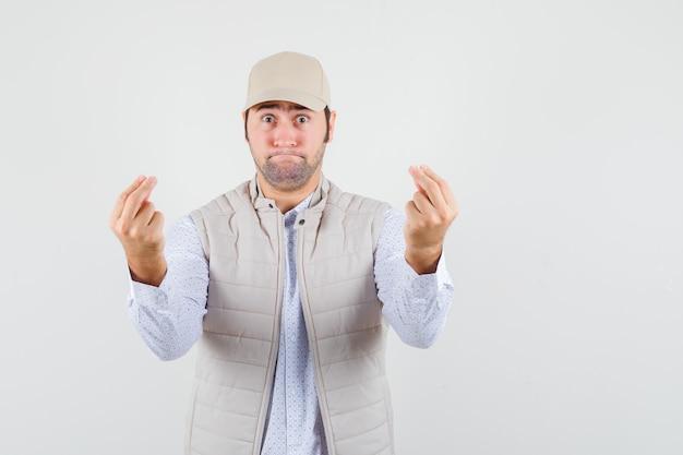 Jeune homme montrant de l'argent avec les deux mains en veste beige et casquette et à la vue de face, heureux.