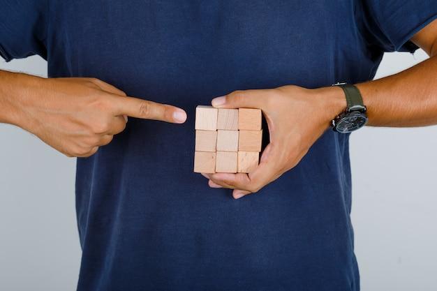 Jeune homme montrant des blocs de bois en vue de face de t-shirt bleu foncé.