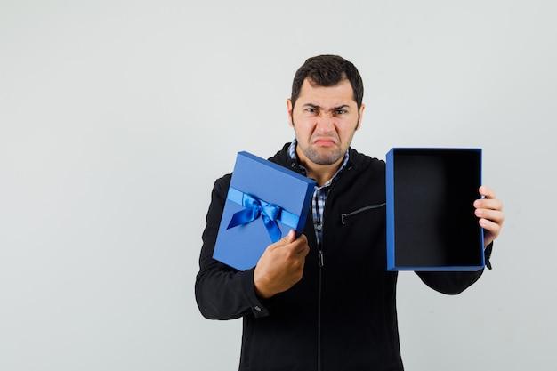Jeune homme montrant une boîte cadeau vide en chemise, veste et à la déçu, vue de face.