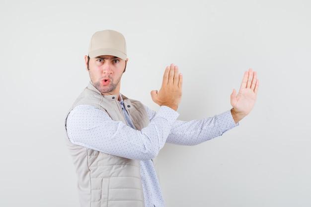 Jeune homme montrant la côtelette de karaté en chemise, veste sans manches, casquette et à la flexibilité. vue de face.