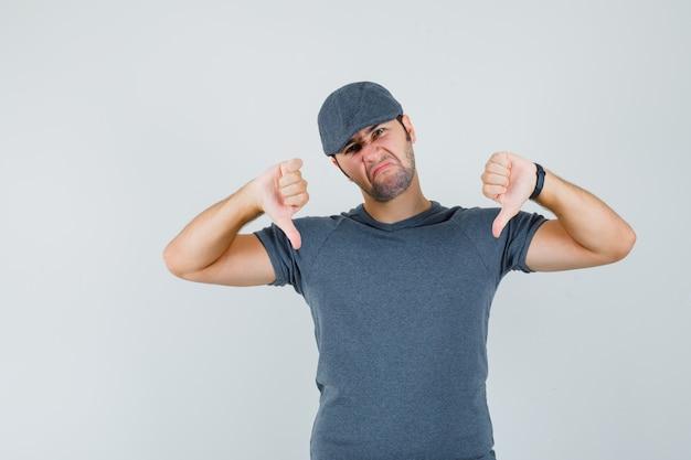 Jeune homme montrant deux pouces vers le bas en casquette t-shirt gris et à la déception