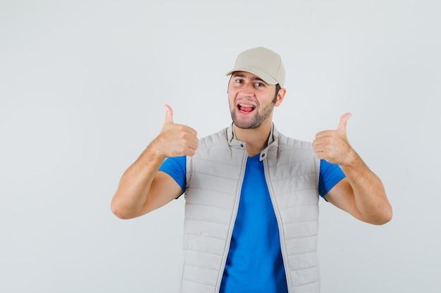 Jeune homme montrant deux pouces vers le haut en t-shirt, veste, casquette et l'air heureux. vue de face.
