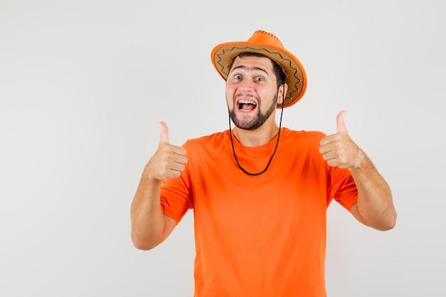 Jeune homme montrant un double pouce levé en t-shirt orange, un chapeau et l'air chanceux. vue de face.