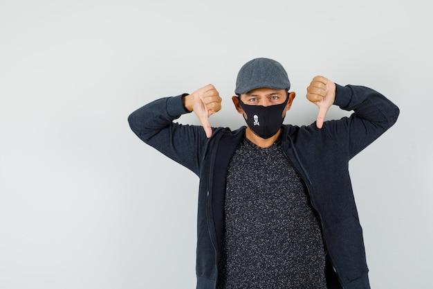 Jeune homme montrant le double pouce vers le bas en t-shirt, veste, casquette, masque