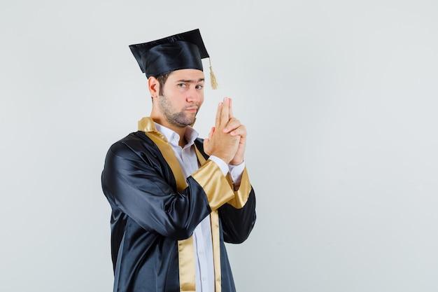 Jeune homme montrant le geste des armes à feu en uniforme diplômé et à la vue de face, confiant.