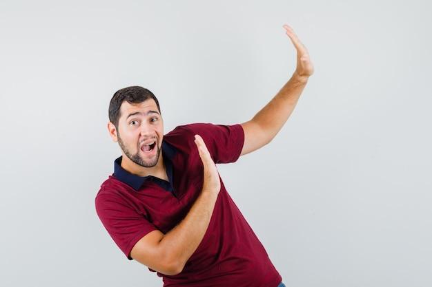 Jeune homme montrant le geste d'arrêt à côté en t-shirt rouge et à la peur, vue de face.