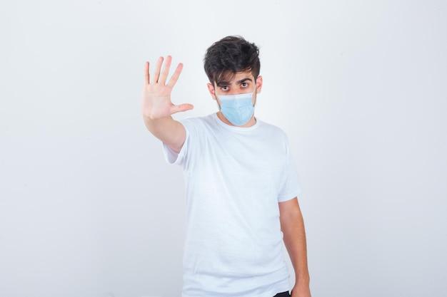 Jeune homme montrant un geste d'arrêt en t-shirt blanc, masque et semblant confiant