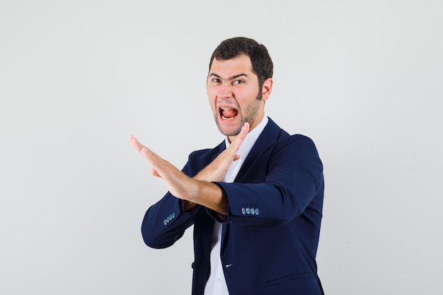 Jeune homme montrant le geste de côtelette de karaté en chemise