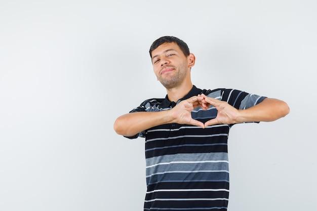 Jeune homme montrant le geste du cœur en t-shirt et l'air joyeux. vue de face.