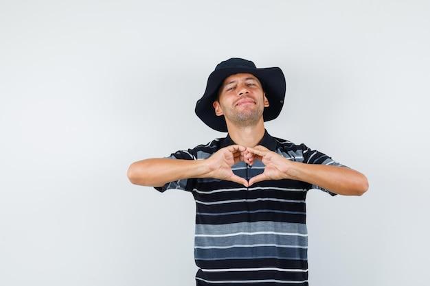 Jeune homme montrant le geste du cœur en t-shirt, chapeau et l'air joyeux, vue de face.