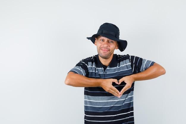 Jeune homme montrant le geste du cœur en t-shirt, chapeau et à la gaieté, vue de face.