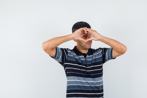 Jeune homme montrant le geste du cœur en t-shirt et regardant gai, vue de face.