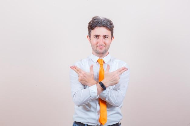 Jeune homme montrant le geste du pistolet en chemise blanche, cravate et à l'air confiant