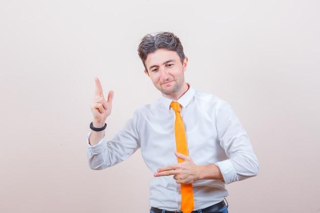 Jeune homme montrant le geste du pistolet en chemise blanche, cravate, jeans et à l'air confiant