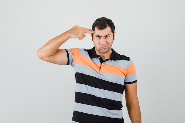 Jeune homme montrant le geste du pistolet sur sa tête en t-shirt et à l'ennui, vue de face. espace pour le texte