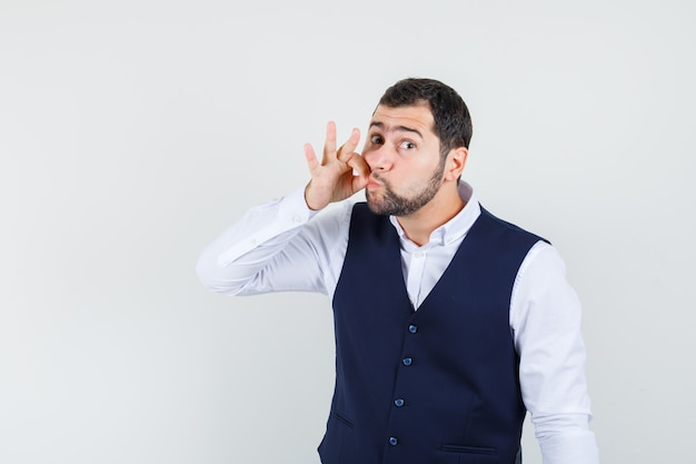 Jeune homme montrant le geste de la fermeture éclair en chemise et gilet et l'air inquiet