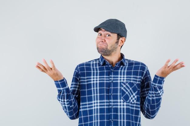 Jeune homme montrant un geste impuissant en chemise, casquette et à la joyeuse vue de face.