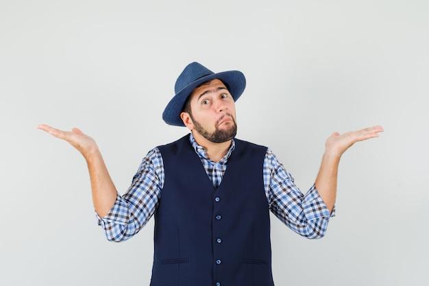 Jeune homme montrant un geste impuissant en chemise, gilet, chapeau et à la confusion.