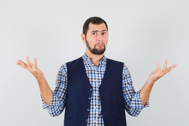 Jeune homme montrant un geste impuissant en chemise, gilet et à la confusion
