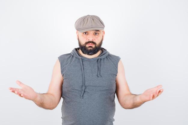 Jeune homme montrant un geste impuissant dans un sweat à capuche sans manches, une casquette et l'air désespéré. vue de face.