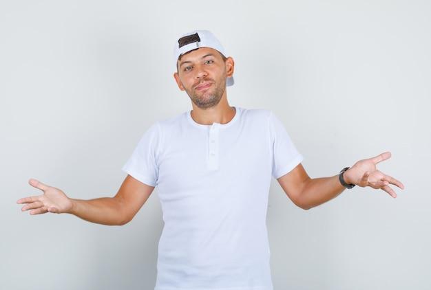 Jeune homme montrant un geste impuissant avec les mains en t-shirt blanc, casquette et à la confusion, vue de face.